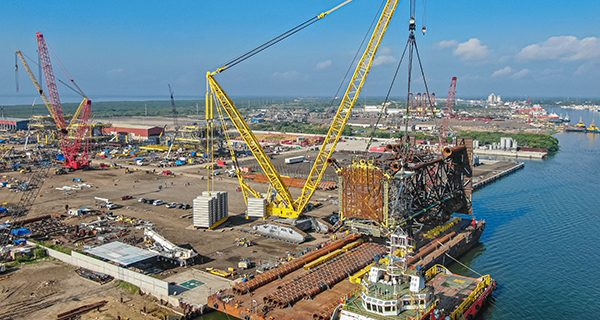 A crawler crane has loaded gigantic oil platforms weighing up to 1200 tonnes each onto barges in just three hours.